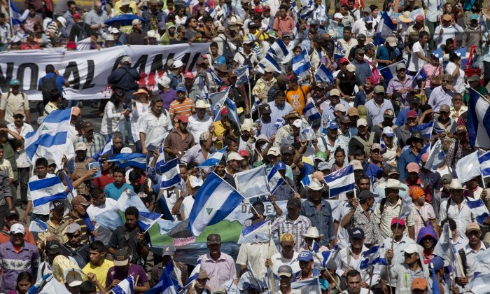People takes part in a national march against the construction of the planned Nicaraguan interoceanic canal, in Managua, Nicaragua, Wednesday, Dec. 10, 2014. Building of the first phase of the multi-billion dollar, 173-mile canal starts on Dec. 22. (AP Photo/Esteban Felix)