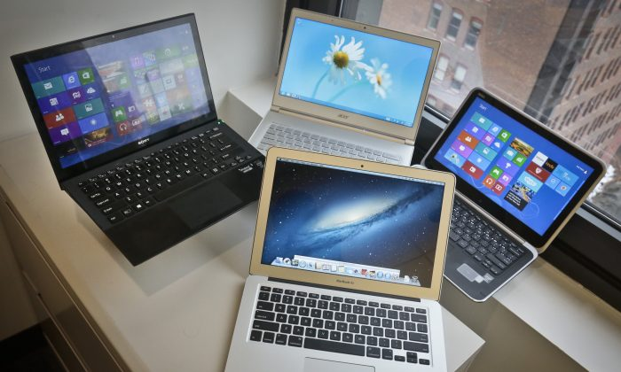 A MacBook Air from Apple, bottom center, a Vaio Pro 13 from Sony, top left, an Aspire S7 from Acer, center, and an XPS 12 from Dell, right, are displayed for a photograph, Thursday, Aug. 22, 2013, in New York. (Bebeto Matthews/AP Photo)