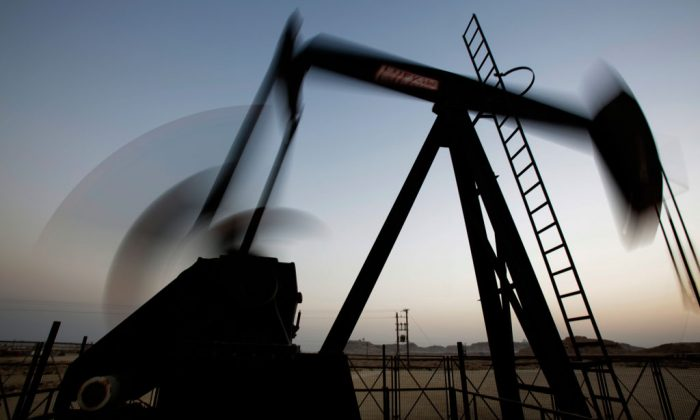 An oil pump works at sunset in the desert oil fields of Sakhir, Bahrain, on Oct. 14, 2014. The price of oil took another sharp tumble Thursday, Nov. 13, 2014, as it appeared increasingly unlikely that OPEC members will cut production to staunch a plunge in prices that is entering its fifth month. (AP Photo/Hasan Jamali)