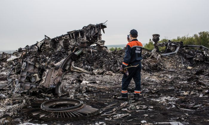 An emergency services worker photographs debris from the crash site of Malaysia Airlines flight MH17 on July 18, 2014 in Grabovka, Ukraine. (Brendan Hoffman/Getty Images)