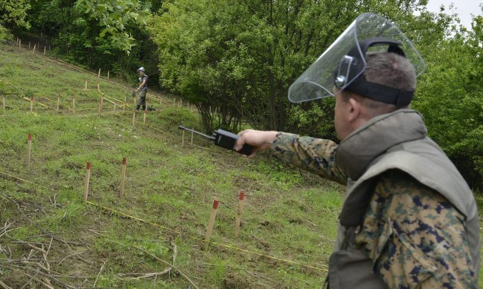 Bosnian soldiers repair warning signs and search for landmines in fields near the banks of the river Bosnia which flooded a town near Sarajevo, May 20. The flooding unearthed landmines left over from Bosnia's 1992-95 war and washed away the signs that marked them. (AP Photo/Sulejman Omerbasic)