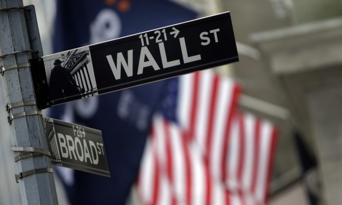 A Wall Street sign adjacent to the New York Stock Exchange, Thursday, Oct. 2, 2014. (AP Photo/Richard Drew)