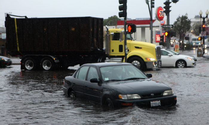 Mark Kunze of San Bruno stalls his car in the flooded intersection of Airport Blvd. and Grand Ave. in South San Francisco, on Thursday, Dec. 11, 2014. Several vehicles stalled in and around the intersection after driving through the deep water. A powerful storm churned through the San Francisco Bay Area on Thursday, knocking out power to tens of thousands and delaying commuters while bringing a soaking of much needed rain.  (AP Photo/Alex Washburn)