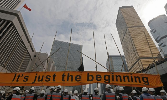 Workers clear barricades on a main road in an occupied area outside government headquarters in Hong Kong's Admiralty district Thursday, Dec. 11, 2014. (AP Photo/Vincent Yu)