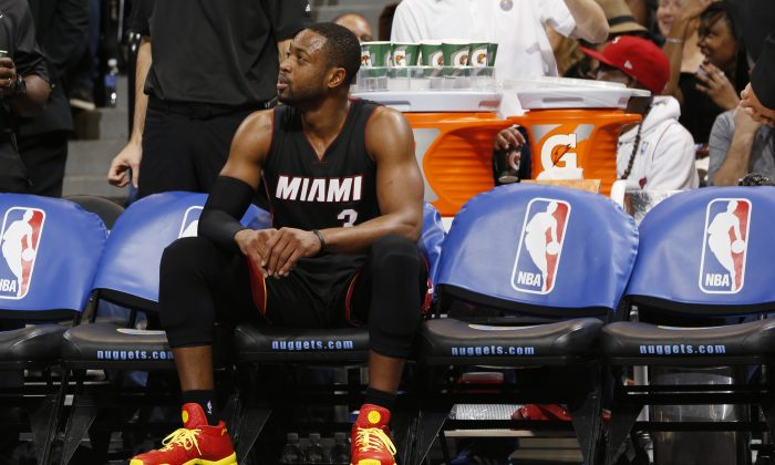 Miami Heat guard Dwyane Wade sits on the bench during a timeout against the Denver Nuggets in the third quarter of the Nuggets' 102-82 victory in an NBA basketball game in Denver on Wednesday, Dec. 10, 2014. (AP Photo/David Zalubowski)