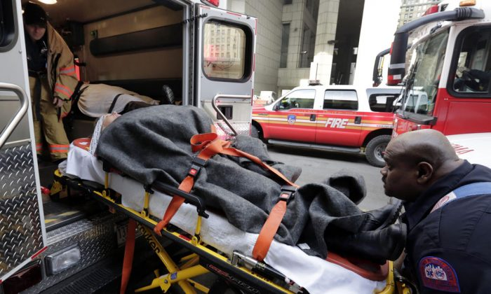 An injured passenger of a New Jersey ferry is loaded into an ambulance, in New York, on Jan. 9, 2013. Nearly 20 percent of U.S. consumers — 42.9 million people — have unpaid medical debts, according to a new report released Thursday, Dec. 11, 2014, by the Consumer Financial Protection Bureau. The findings suggest that many Americans lack the financial resources to pay for health emergencies — and that the notices from hospitals and insurance companies about the cost of treatment are confusing and baffling. (AP Photo/Richard Drew)
