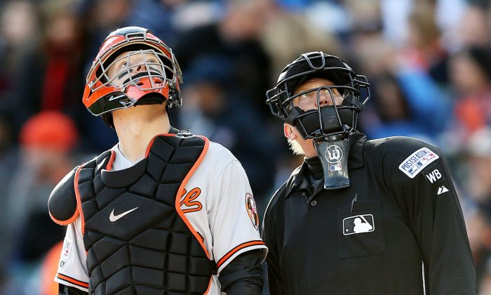 Nick Hundley of the Baltimore Orioles and umpire Jeff Kellogg look up at Comerica Park in Detroit on Oct. 5, 2014. (Leon Halip/Getty Images)