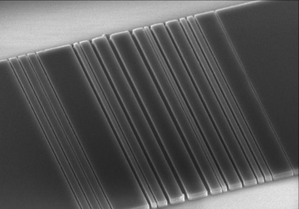 This tiny slice of silicon, etched in Jelena Vuckovic's lab at Stanford with a pattern that resembles a bar code, is one step on the way toward linking computer components with light instead of wires. (Stanford Vuckovic Lab)