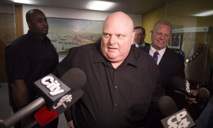 Toronto's outgoing Mayor Rob Ford (centre) stands next to his brother Doug Ford (right) outside his office as he scrums with the media before signing bobble heads in Toronto on Nov. 21, 2014. Rob Ford says he's due for a fifth round of chemotherapy next week but that if he beats cancer he'll take another run for mayor of Toronto. (The Canadian Press/Chris Young)