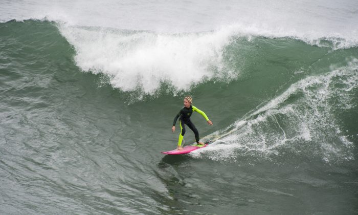 A young surfer catches one of the bigger waves in the morning in Huntington Beach on Thursday morning Dec. 11, 2014. A powerful storm churned down the West Coast on Thursday, bringing strong gales and much-needed rain and snow that caused widespread blackouts in Northern California and whiteouts in the Sierra Nevada.   (AP Photo/The Orange County Register, Michael Goulding)