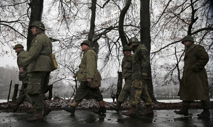 Re-enactors dressed as US WWII soldiers walk along a road during the 70th anniversary of the Battle of the Bulge or the Ardennes Offensive, in Bastogne, southeastern Belgium, Saturday, Dec. 13, 2014. The Battle of the Bulge was fought in dense forests and narrow valleys of the Belgian and Luxembourg Ardennes and was one of the bloodiest battles of World War II. (AP Photo/Yves Logghe)
