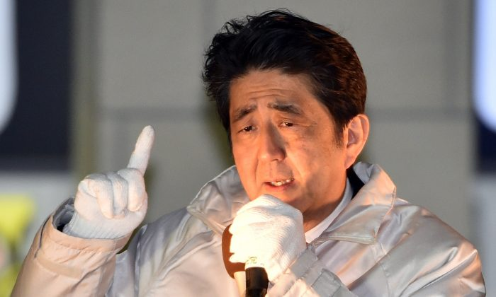 Japanese Prime Minister and ruling Liberal Democratic Party (LDP) leader Shinzo Abe delivers a campaign speech for the upcoming general election before his party supporters at Omiya, Tokyo, on Dec.  9, 2014. (Yoshikazu Tsuno/AFP/Getty Images)