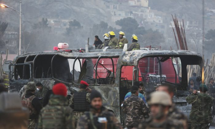 Afghan security personnel inspect a damaged bus at the site of a suicide attack by the Taliban in Kabul, Afghanistan, on Dec. 13, 2014. (AP Photo/Rahmat Gul)