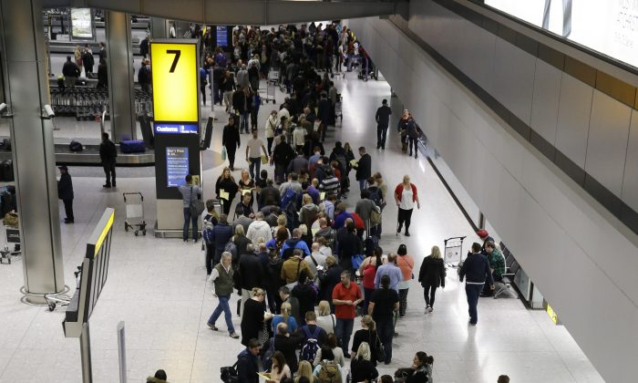 People queue in the luggage hall of Terminal 5 at Heathrow Airport in London, Friday, Dec. 12, 2014. London's airspace was closed today due to what authorities say was a computer failure at one of Britain's two air traffic control centres. Britain's national air traffic body says the computer problem that touched off troubles in the system has been fixed and it is in the process of returning to normal operations. (AP Photo/Matt Dunham)