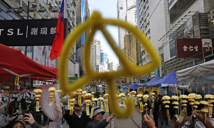 Yellow umbrella decorations are hanged by protesters in the Causeway Bay shopping district, one of the occupied areas by pro-democracy protesters in Hong Kong Saturday, Dec. 13, 2014. (AP Photo/Kin Cheung)