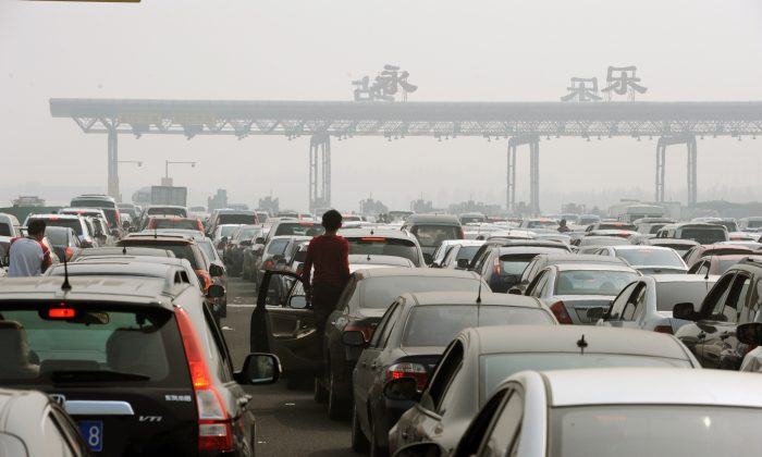 Chinese motorists get out of their cars to check on a massive traffic jam at a toll booth on the outskirts of Beijing on Oct. 2, 2010. In 2014 an estimated 400 billion yuan in tolling fees was paid by Chinese drivers, and many have questioned the legality of current toll policies. (STR/AFP/Getty Images)