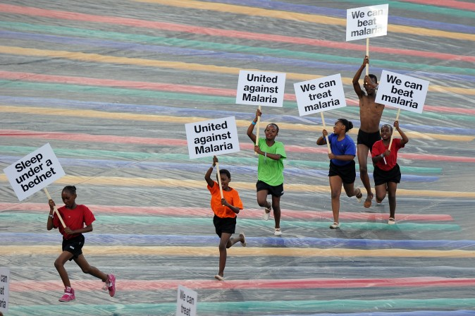 Children run with advertising banners for the fight against malaria. (Photo credit should read Alexander Joe/AFP/Getty Images)