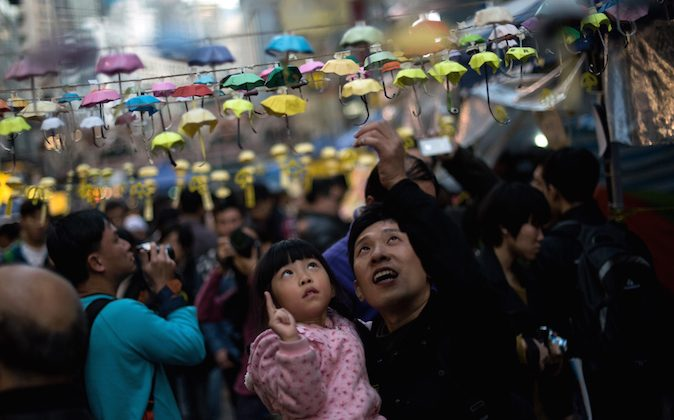 A man and his daughter pose for photos next to an installation of paper umbrellas -- symbols of the pro-democracy protests in Hong Kong -- in the Causeway Bay district of Hong Kong on December 14, 2014. (Alex Ogle/AFP/Getty Images)