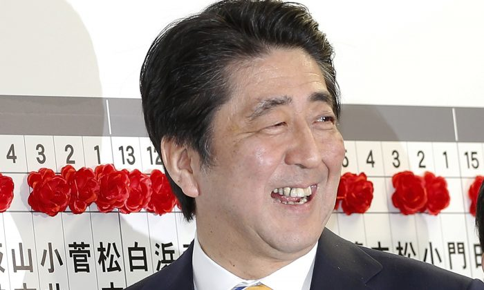 Japanese Prime Minister Shinzo Abe, leader of the Liberal Democratic Party, smiles as he places a red rosette on the name of his Liberal Democratic Party's winning candidate during ballot counting for the lower  house elections at the party headquarters in Tokyo, Sunday, Dec. 14, 2014. Japan's ruling coalition was headed for a landslide victory in lower house elections Sunday, firming up Abe's hold on power as he prepares to push forward on several politically difficult fronts. (AP Photo/Shizuo Kambayashi)