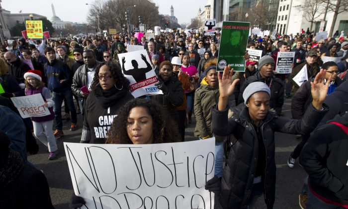 Demonstrators march on Pennsylvania Avenue toward Capitol Hill in Washington, Saturday, Dec. 13, 2014, during the Justice for All rally. More than 10,000 protesters are converging on Washington in an effort to bring attention to the deaths of unarmed black men at the hands of police. Civil rights organizations are holding a march to the Capitol on Saturday with the families of Michael Brown and Eric Garner, two unarmed black men who died in incidents with white police officers. (AP Photo/Jose Luis Magana)