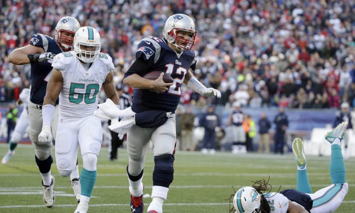New England Patriots quarterback Tom Brady (12) runs with the ball as Miami Dolphins defensive end Olivier Vernon (50) gives chase in the second half of an NFL football game, Sunday, Dec. 14, 2014, in Foxborough, Mass. (AP Photo/Steven Senne)