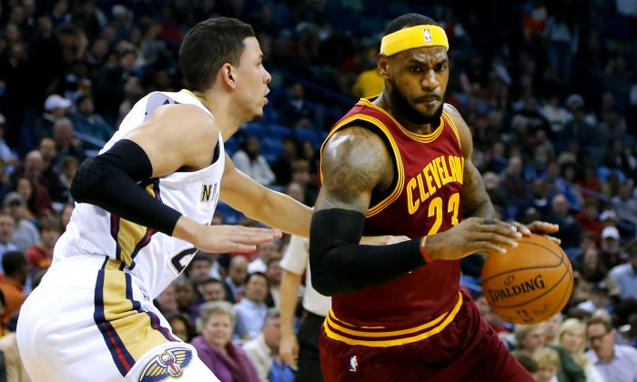 Cleveland Cavaliers forward LeBron James (23) drives against New Orleans Pelicans guard Austin Rivers, left, during an NBA basketball game in New Orleans, Friday, Dec. 12, 2014. (AP Photo/Jonathan Bachman)