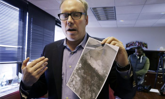 Toms River, N.J., resident Douglas Quinn in Newark, N.J., on Nov. 14, 2014, showing a photo of damage to his home after Superstorm Sandy. He says that his insurance company now says that the damage was pre-existing and refuses his claim. (AP Photo/Mel Evans)