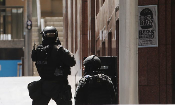 Police stand at the ready close to a cafe under siege in Martin Place in the central business district of Sydney, Australia, Monday, Dec. 15, 2014. (AP Photo/Rob Griffith)