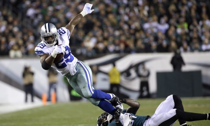 Dallas Cowboys' DeMarco Murray (29) tries to break free from a tackle by Philadelphia Eagles' Malcolm Jenkins (27) during the first half of an NFL football game, Sunday, Dec. 14, 2014, in Philadelphia. (AP Photo/Michael Perez)
