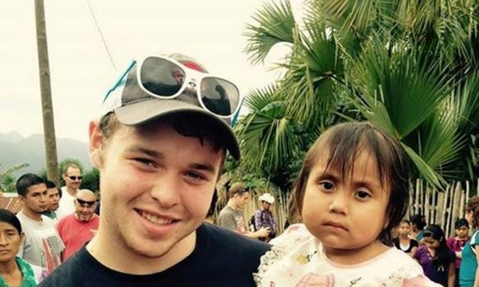 Joseph Duggar with a child in Central America on a mission trip. (Duggar Family Blog)