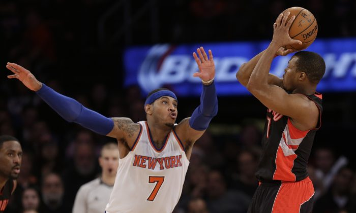 Toronto Raptors' Kyle Lowry, right, shoots while New York Knicks' Carmelo Anthony tries to defend during overtime of the NBA basketball game, Sunday, Dec. 14, 2014 in New York. The Raptors beat the Knicks in overtime 95-90. (AP Photo/Seth Wenig)