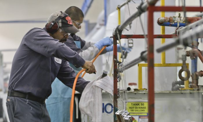 Employees at Sheffield Platers Inc. work on the factory floor in San Diego, Calif. on Oct. 10, 2013. (AP Photo/Lenny Ignelzi)