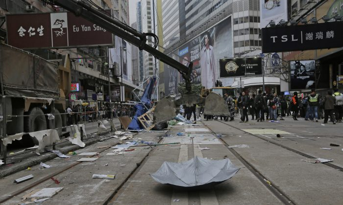 An excavation shovel is lowered to pick up an umbrella left behind by protesters as police clear barricades and tents on a main road in the occupied areas at Causeway Bay district in Hong Kong Monday, Dec 15, 2014. (AP Photo/Vincent Yu)
