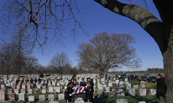 Service members fold an American flag over a casket containing the remains of Anthony La Rossa in Farmingdale, N.Y., on Monday, Dec. 15, 2014. The 18-year-old New York City soldier listed for decades as missing in action during the Korean War received full military honors at a funeral Monday on Long Island. (AP Photo/Seth Wenig)