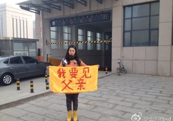 "College girl Bian Xiaohui holds a banner that says ""I want to see my father"" on street on March 3, 2014. Bian and her cousin who took the photo have been detained, and went on trial on Dec. 12 being accused for ""publicizing Falun Gong persecution"" by putting the photo online. (Screenshot/Weibo.com)"