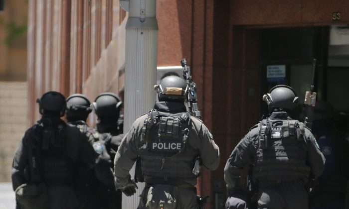 Armed police stand at the ready close to a cafe under siege at Martin Place in Sydney, Australia, Monday, Dec. 15, 2014. (AP Photo/Rob Griffith)