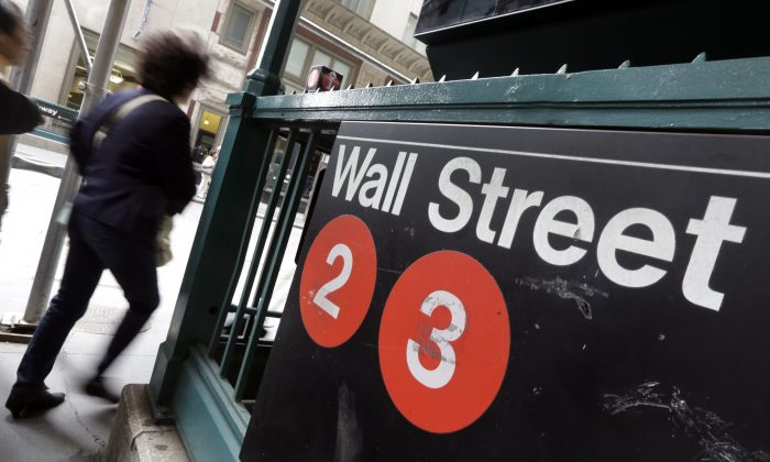 People pass a Wall Street subway stop, in New York's Financial District on Oct. 2, 2014. U.S. stocks are opening moderately lower Tuesday, Dec. 16, 2014, as the price of oil continues to drop. (AP Photo/Richard Drew)