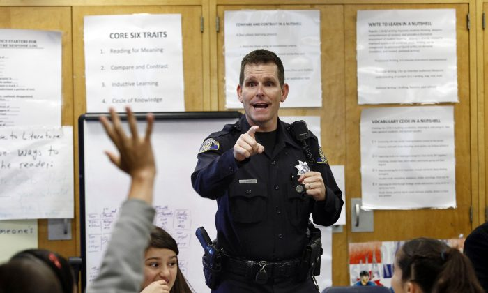 "In this Tuesday, Oct. 28, 2014 file photo, Officer Phil White of the San Jose Police Department teaches a ""Choices and Consequences"" class for 5th grade students at Christopher Elementary School in San Jose, Calif. White is on leave as his department investigates comments posted online that threaten those protesting the recent deaths of unarmed black men in Ferguson, Missouri, and New York. In the tweets, White said he would kill anyone who threatens him or his family. He also said he would be off-duty at the movies with his gun if anyone ""feels they can't breathe or their lives matter."" (AP Photo/Bay Area News Group, Gary Reyes)"