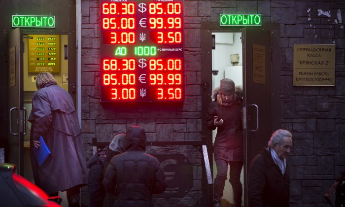 People wait to exchange their currency as signs advertise the exchange rates at a currency exchange office in Moscow, Russia, Tuesday, Dec. 16, 2014. The Russian ruble came under intense selling pressure Tuesday, falling at one point by a catastrophic 20 percent to a new historic low despite a massive pre-dawn interest rate hike from Russia's Central Bank. Russian officials were clearly rattled even though state television urged citizens not to panic.The top two figures indicate the spread on the dollar-ruble rate and the middle two figures indicate the euro-ruble rate, with the third showing the spread on the Ukrainian hryvnia-ruble rate. (AP Photo/Alexander Zemlianichenko)