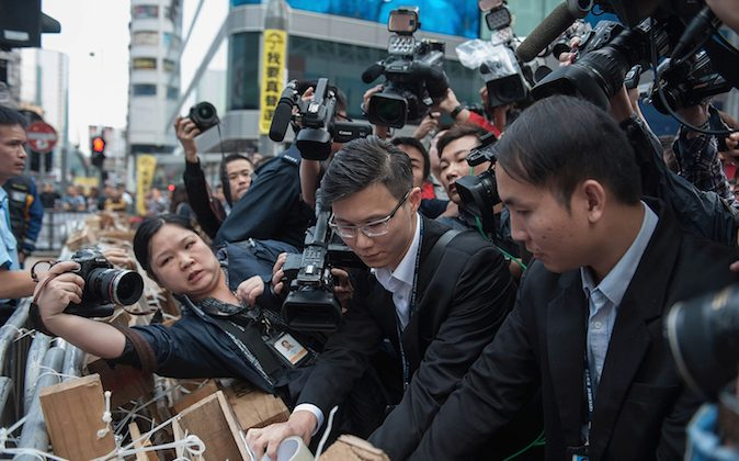 Court bailiffs post a copy of the injunction order on Argyle Street in Mongkok district on November 19, 2014 in Hong Kong. Chiu Luen Public Light Bus Company obtained the injunction for Argyle Street and it was published on newspaper to notify the occupiers. (Anthony Kwan/Getty Images)