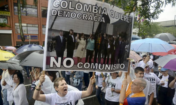 People attend the 'Peace without Impunity' march, against the current peace talks with FARC rebels in Medellin, a sign reads 'Colombia wants democracy, not communism', Antioquia department, on Dec. 13, 2014. Hundreds of people marched Saturday in several cities in Colombia to question the peace negotiations between the government of President Juan Manuel Santos and the FARC guerrillas. (Raul Arboleda/AFP/Getty Images)