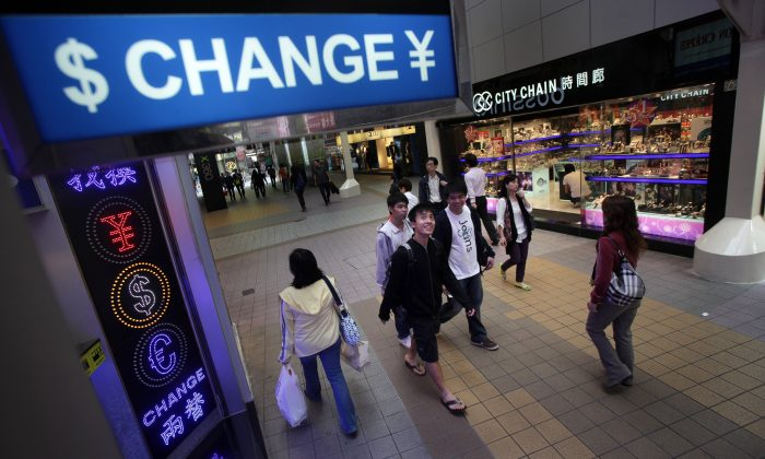 People walk past a currency exchange shop in the Causeway Bay area of Hong Kong on April 28, 2010. (Ed Jones/AFP/Getty Images)