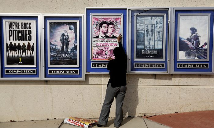 "A poster for the movie ""The Interview"" is taken down by a worker after being pulled from a display case at a Carmike Cinemas movie theater in Atlanta on Dec. 17. (AP Photo/David Goldman)"