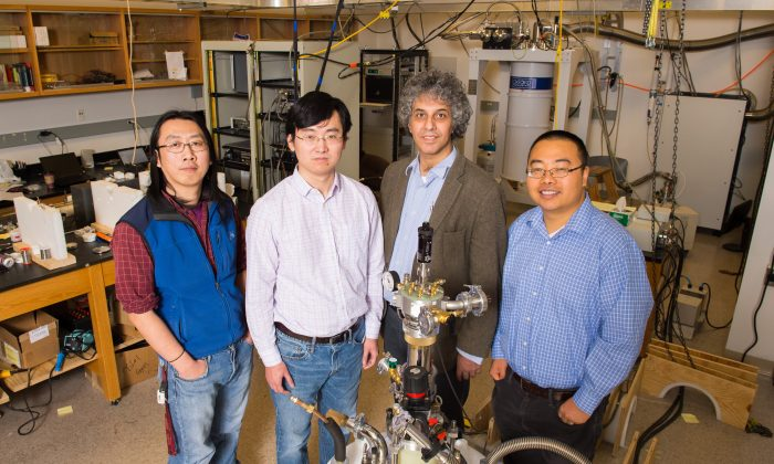 Physics researchers at the University of Michigan have confirmed the strange electrical behavior of a material called samarium hexaboride. The compound, it turns out, is a topological insulator. Gang Li, postdoctoral researcher; Kai Sun, assistant professor; Cagliyan Kurdak, professor; and Lu Li, assistant professor, stand in front of their experimental set-up. (Daryl Marshke/Michigan Photography)