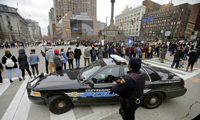 File - In this Nov. 25, 2014 file photo, Cleveland police watch demonstrators block Public Square while protesting against the shooting of 12-year-old boy Tamir Rice, who was fatally shot by a police officer in Cleveland. The revelation that Cleveland police officials didn't review the checkered history of a police officer who fatally shot a 12-year-old boy highlights what some describe as an unnerving truth about policing -- there's no universal standard for how deeply a department should dig into its recruits' pasts. (AP Photo/Mark Duncan, file)