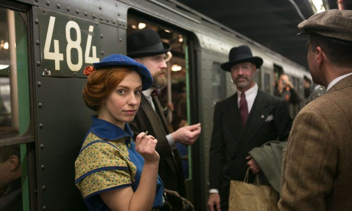 People donning early- and mid-20th century fashion stand in the doorway of a vintage MTA subway train, which only runs during the holidays, in Manhattan on Dec. 14, 2014. The event includes live jazz bands and dancing. (Benjamin Chasteen/Epoch Times)