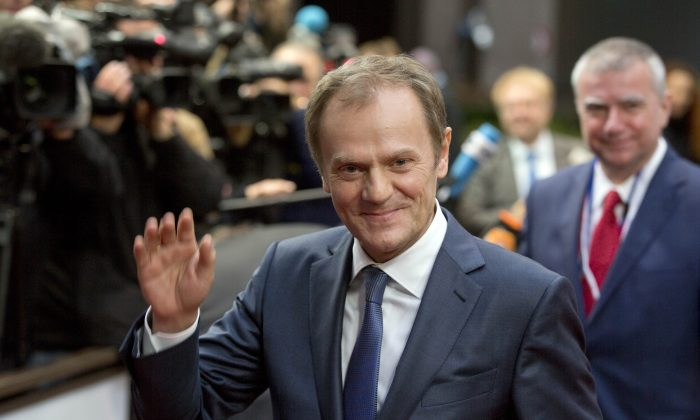 European Council President Donald Tusk waves as he arrives for an EU summit in Brussels on Thursday, Dec. 18, 2014. European Union leaders met Thursday to seek solutions to two major challenges, how to jumpstart sluggish economic growth at home, and how to deal long-term with Russia. (AP Photo/Virginia Mayo)
