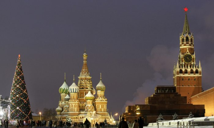 In this Thursday, Dec. 10, 2009 file photo people walk past a huge Christmas tree installed in Red Square, with St. Basil Cathedral,  center, the Kremlin's Spassky Tower, right back, and Lenin Mausoleum, right, in Moscow, Russia. (AP Photo/Misha Japaridze)