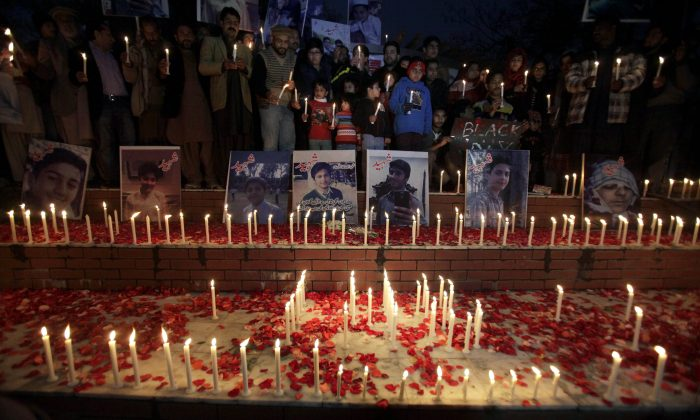 Local residents place candles around portraits of the victims killed in Tuesday's Taliban attack on a military-run school in Peshawar, at a ceremony in Islamabad, Pakistan, Thursday, Dec. 18, 2014. The Taliban massacre that killed more than 140 people, mostly children, at the military-run school in northwestern Pakistan left a scene of heart-wrenching devastation, pools of blood and young lives snuffed out as the nation mourned and mass funerals for the victims got underway. (AP Photo/Anjum Naveed)