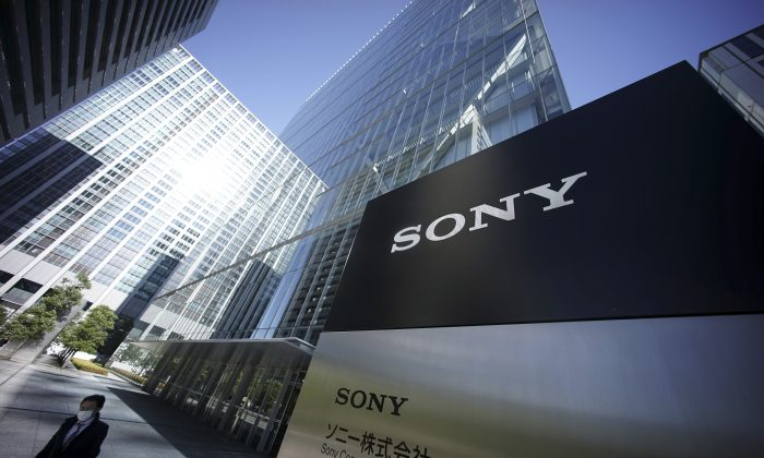 """A man walks at the headquarters of Sony Corp. in Tokyo, Dec. 18. Sony's share prices jumped 5 percent on Wednesday after it canceled the release of """"The Interview,"""" which is believed to have provoked the recent hacking. (AP Photo/Eugene Hoshiko)"""